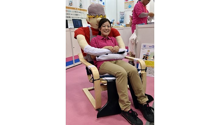 An employee of Japan's nursing care goods maker UniCare demonstrating an easy chair for congnitively impaired persons at the annual International Home Care and Rehabilitation exhibition in Tokyo. AFP